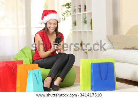 Girl texting greeting sms on mobile phone with colorful shopping bags at home - stock photo