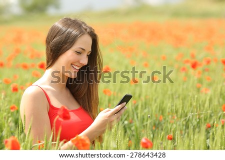 Girl texting in a smart phone in a colorful field with red flowers - stock photo