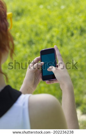 Girl Texting on her Smart Phone, Closeup  - stock photo