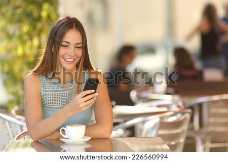 Girl texting on the smart phone in a restaurant terrace with an unfocused background - stock photo