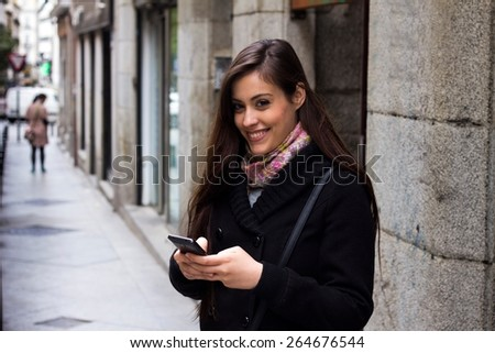 Girl texting on the street - stock photo