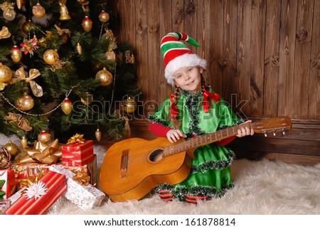 Girl - the Christmas elf with a guitar near Xmas fir-tree - stock photo