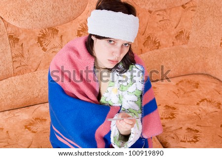girl thermometer on the couch wrapped in a blanket - stock photo
