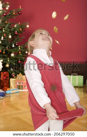 Girl throwing chocolate coins in air - stock photo