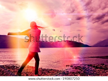 girl throwing stones into a lake in sunset - stock photo