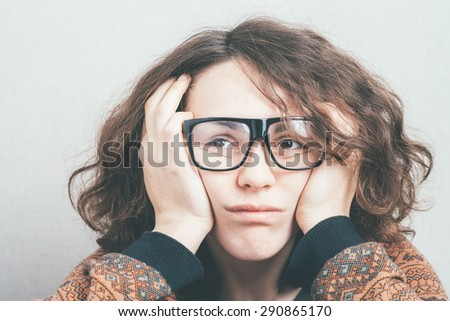 Girl tired and holding his head with glasses - stock photo