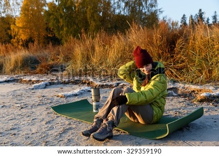 Girl tourist in insulated clothes sitting on a coast