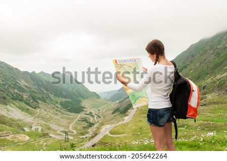 Girl tourist in mountain read the map. Transfagarasan road from Romania! - stock photo