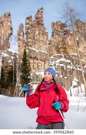 Girl tourist in winter on a background of red rocks, Ural mountains - stock photo