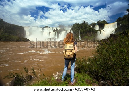 girl tourist looks at the  view of worldwide known Iguassu falls at the border of Brazil and Argentina