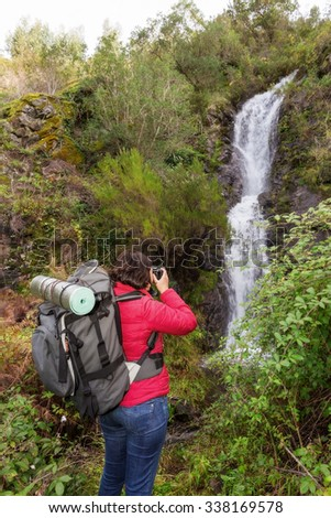 Girl tourist photographing a waterfall. In Portugal, the village Monchique. - stock photo