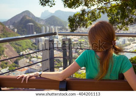 girl tourist sitting and resting on the bench on the background Rio de Janeiro. view from Pao de Acucar