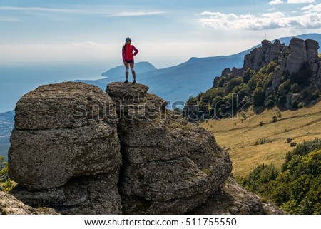 Girl tourist standing on a big cliff, Crimea