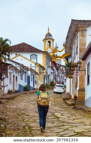 Girl tourist walks in the streets of the famous historical town Tiradentes, Minas Gerais, Brazil