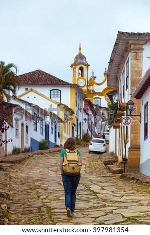 Girl tourist walks in the streets of the famous historical town Tiradentes, Minas Gerais, Brazil  - stock photo