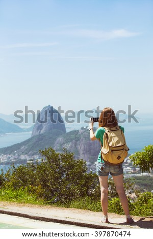 girl tourist with a backpack on the background Rio de Janeiro. view from Pao de Acucar