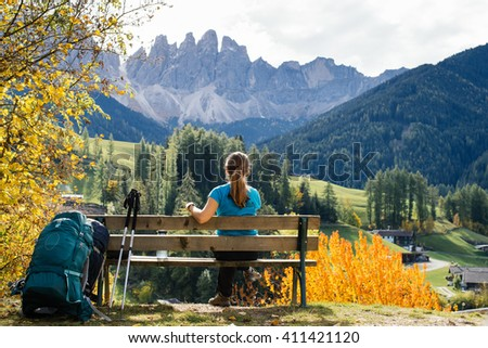 Girl tourist with a backpack sitting on the bench and admiring the incredible views of the mountains in the Alps - stock photo