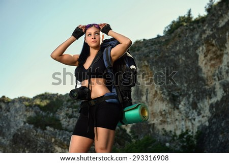 girl tourist with a camera on the background of rocks - stock photo