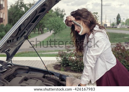 Girl tries to repair the car. She opened the hood and razgyadyvaet parts of the machine. Concept: a road accident, repair