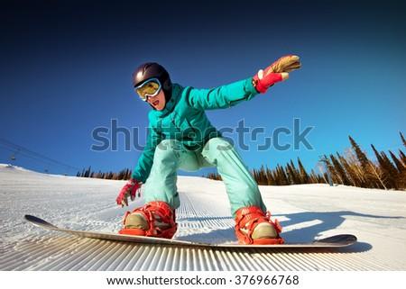 Girl try to improve her snowboarding. Sheregesh resort, Siberia, Russia - stock photo
