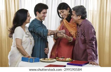 Girl tying a rakhi on her brothers hand - stock photo