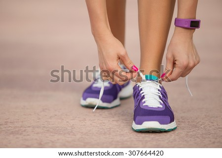 Girl tying running shoes - stock photo