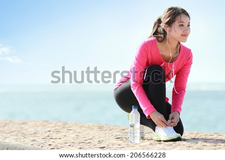 Girl tying shoelaces while doing some exercise on the beach - stock photo