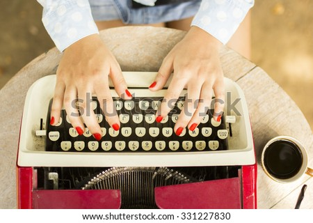 Girl typing on the old typewriter with a cup of coffee outdoors - stock photo