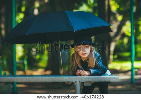Girl under a black umbrella in a hat walking in the park summer day - stock photo