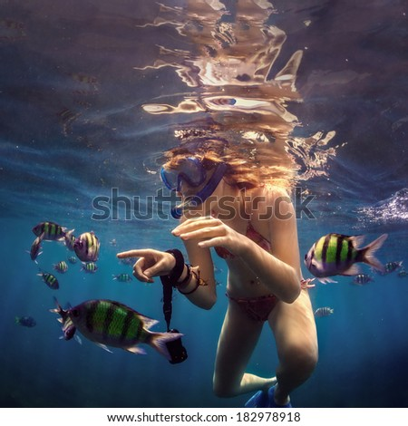 Girl under water with fishes. - stock photo