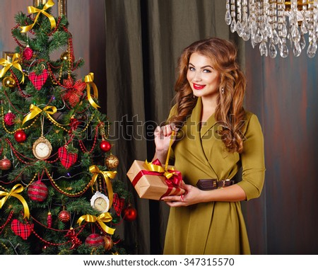 Girl unpacks gift. Christmas tree. New Year. Waiting for a miracle. Merry Christmas. - stock photo
