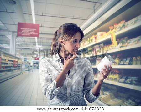 Girl unsure about the authenticity of the product at supermarket - stock photo