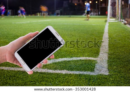 Girl use mobile phone ,blur image of a football field as background. - stock photo