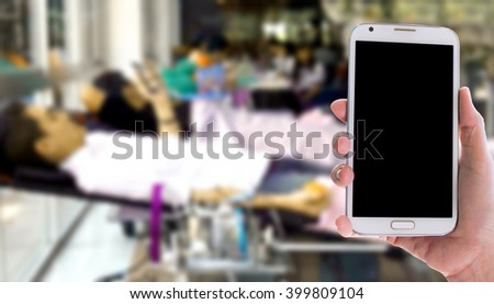 Girl use mobile phone, blur image of blood donation as background. - stock photo