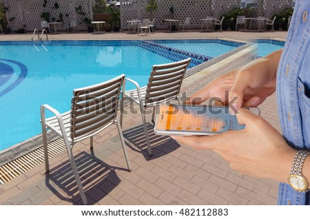 Girl use mobile phone, blur image of the swimming pool as background.