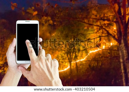 Girl use mobile phone, image of forest fire  at night as background. - stock photo
