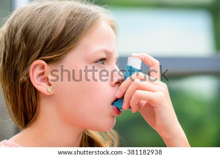 Girl uses an inhaler during an asthma attack, close-up - stock photo