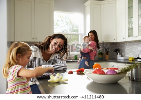 Girl uses tablet in kitchen with mum, other mum holding baby - stock photo