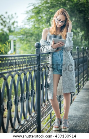 Girl using a digital tablet outdoors. - stock photo