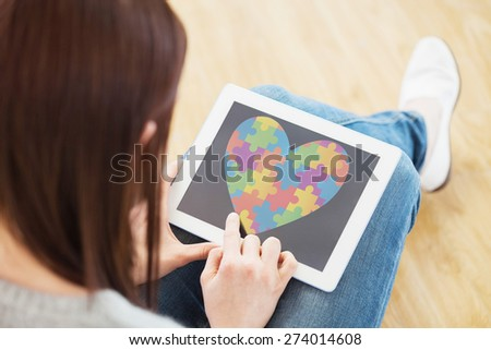 Girl using a tablet pc sitting on the floor against autism awareness heart - stock photo