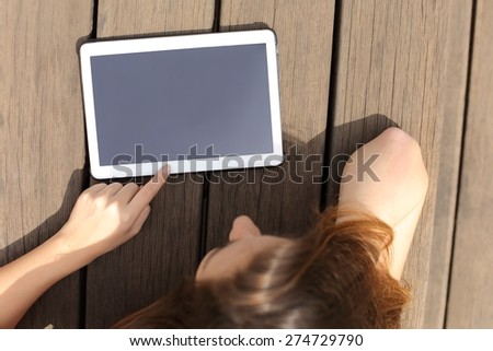 Girl using and showing a blank tablet screen lying in a bench in a sunny day - stock photo