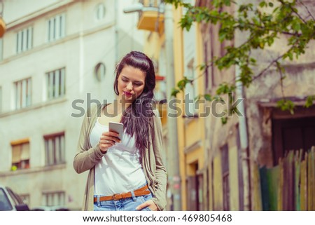 Girl using cellphone outdoors.