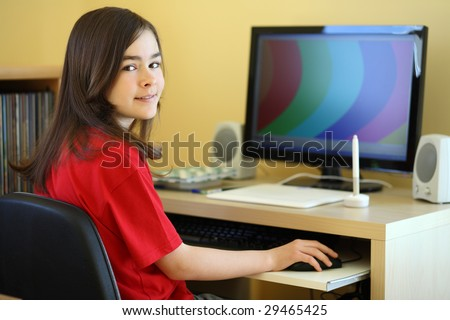 Girl using computer at home - stock photo