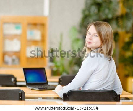 girl using computer in a library. looking at camera - stock photo