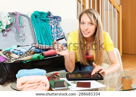 Girl using credit card and tablet for reserving ticket online - stock photo