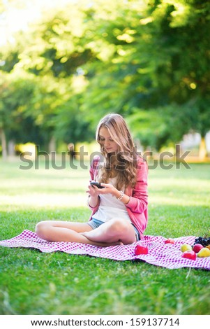 Girl using her mobile phone outdoors - stock photo