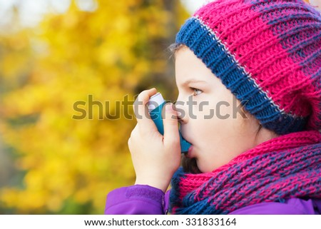 Girl Using Inhaler on an autumn day - to Treat Asthma Attack. Inhalation treatment of respiratory diseases. Shallow depth of field. Allergy concept. Asthma child.  - stock photo