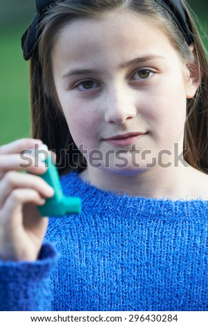 Girl Using Inhaler To Treat Asthma Attack - stock photo