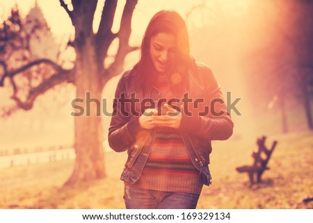 girl using mobile phone outdoor retro colors - stock photo