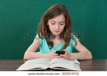 Girl Using Mobile Phone While Studying In Classroom - stock photo